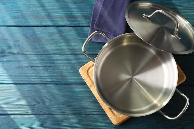 Lege metalen pot op snijplank op houten tafel.