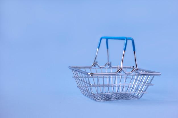 Lege metalen winkelmandje op een blauwe achtergrond
