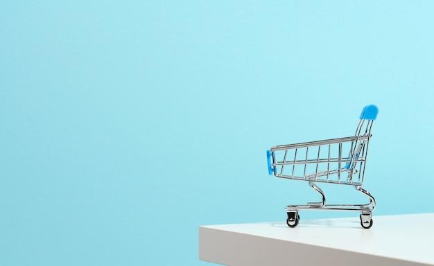 Lege miniatuur winkelwagen op blauwe achtergrond. seizoensgebonden verkoop, kopieerruimte, online winkelen
