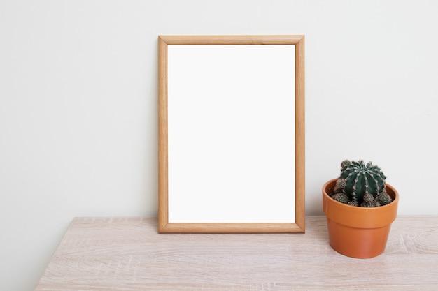 Lege mockup van een houten frame met een cactus in een pot