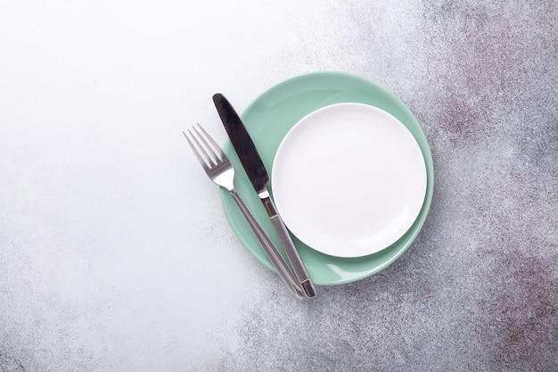 Lege munt en witte platen, mes en vork kopieer ruimte bovenaanzicht