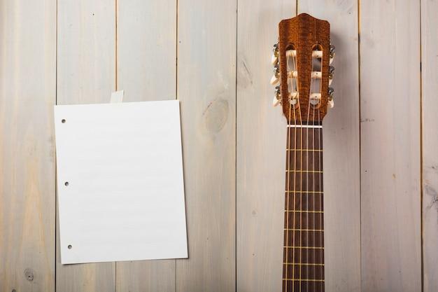 Lege muzikale pagina die op houten muur met het hoofd van de gitaar wordt geplakt