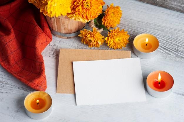 Lege nota en rode aromakaarsen en bloemen op rustieke achtergrond