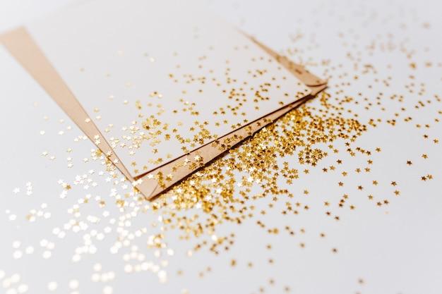 Lege nota met envelop en gouden glittersterren op witte achtergrond