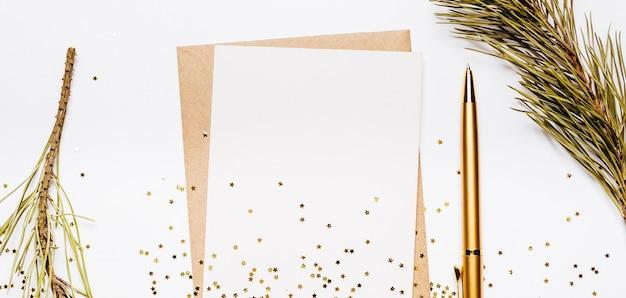 Lege nota met envelop, vuren tak en gouden pen op witte achtergrond