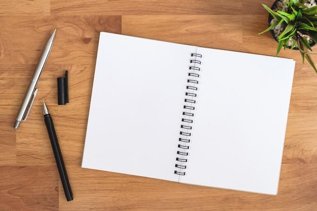 Lege notebook ligt op de top van houten kantoor bureau tafel met pennen.