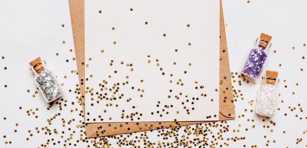 Lege notitie met envelop, geschenken en gouden glitter sterren op witte achtergrond