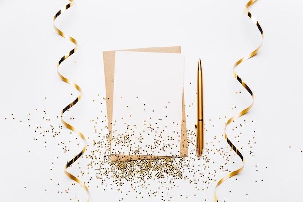 Lege notitie met envelop, lint, confetti, pen en gouden glitter sterren op witte achtergrond