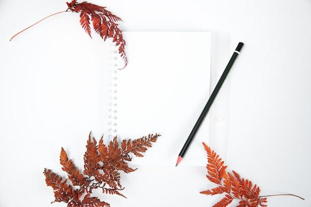 Lege notitieblok op witte achtergrond versierd met herfst plant samenstelling bovenaanzicht plat lag