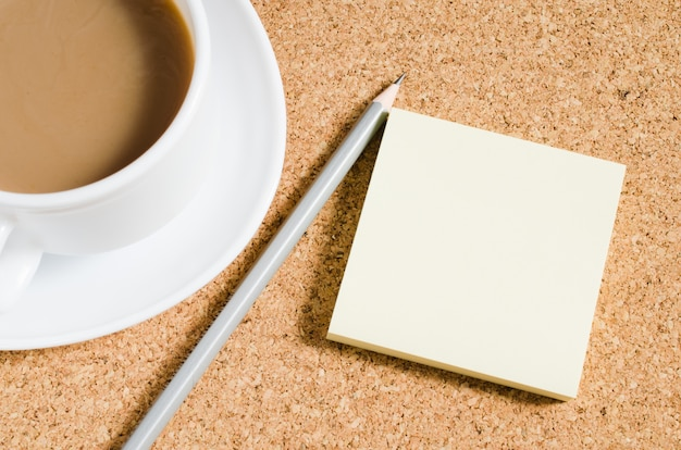 Lege notities en kopje koffie op kurk boord