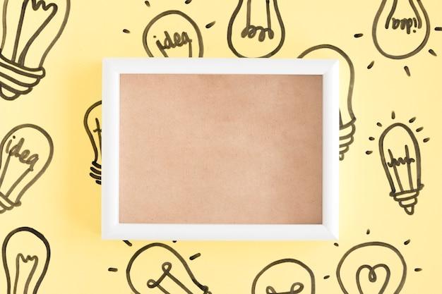 Lege omlijsting die met gloeilampen op gele achtergrond wordt omringd