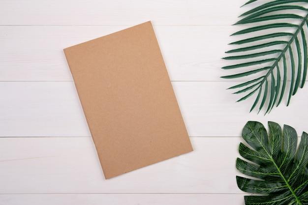 Lege omslag boek kopie ruimte met mockup en blad op houten tafel.