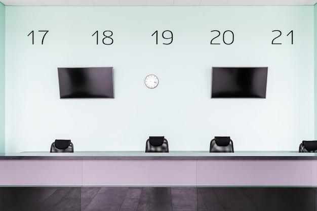 Lege ontvangst zonder beheerder op kantoor. entree business center met bureau en uitgeschakeld tv-toestellen, klok en stand nummers op de muur erachter