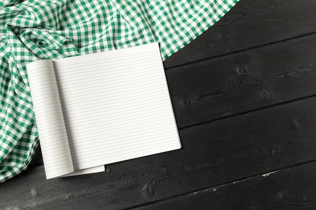Lege open kladblok op houten achtergrond met een stuk doek