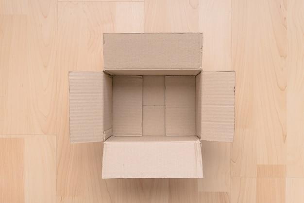 Lege open rechthoekige kartonnen doos op hout achtergrond