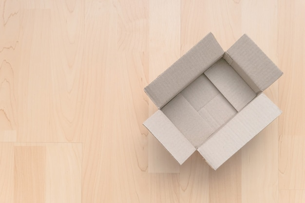 Lege open rechthoekige kartonnen doos op hout. winkelen online object achtergrond. pakketobject verzenden.