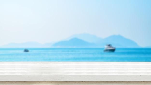 Lege oude donkere houten tafelblad met vervagen blauwe hemel en zee bokeh achtergrond