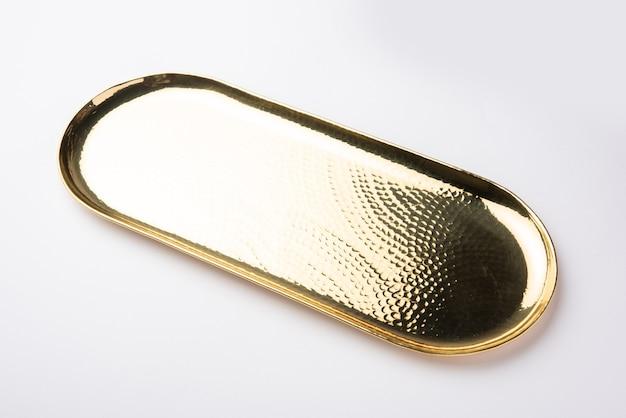 Lege ovale of ronde vorm thali of plaat gemaakt van messing, pital of goud over wit oppervlak