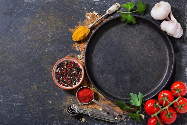 Lege pan met diverse producten om te koken op donkere achtergrond, bovenaanzicht