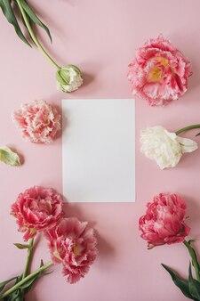 Lege papieren kaart in frame van roze pioenroos bloemen