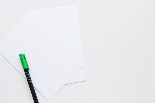 Lege papieren kaart met pen op witte achtergrond voor werkruimte concept