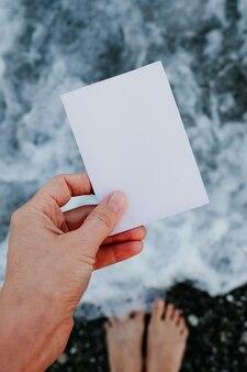 Lege papieren notitie in de hand op verbazingwekkend landschap