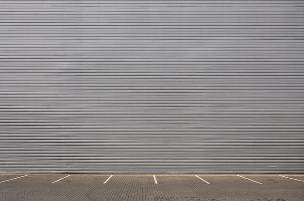 Lege parkeerplaatsen op de achtergrond van een metaalmuur