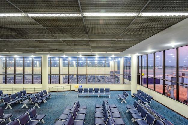 Lege passagierszetel op luchthaven voor wachtend vluchtvertrek in de avond