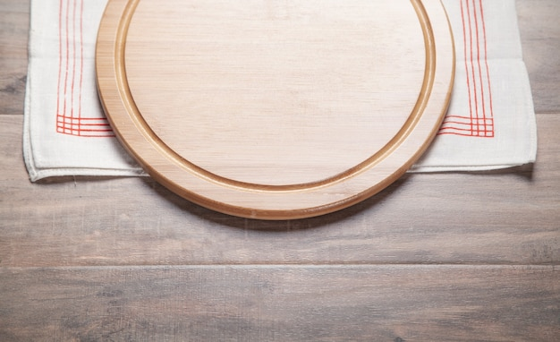 Lege pizza bord en stof tafelkleed op de houten achtergrond.