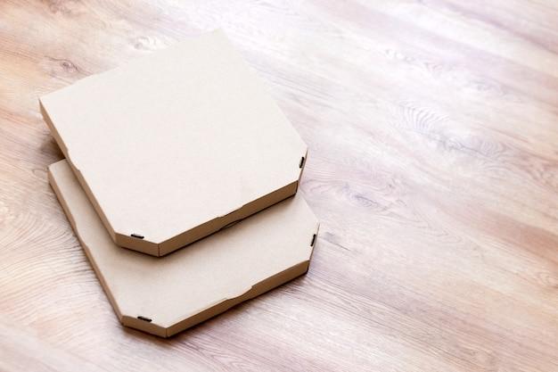Lege pizza-kartonnen dozen. haal de dozen van het pizzabakpapier op houten achtergrond weg. vooraanzicht verpakking voor voedselbezorging.