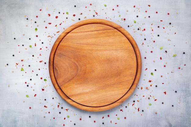 Lege pizzaschotel met kruiden opgesteld op een donkere betonnen ondergrond, plat leggen en kopiëren.