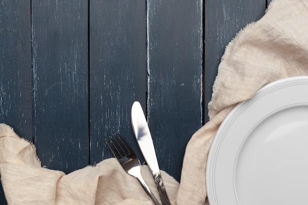 Lege plaat en handdoek over houten tafel achtergrond.