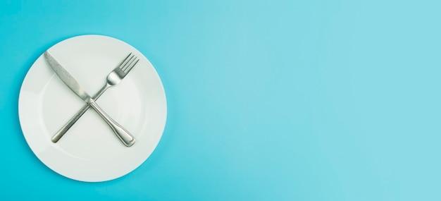 Lege plaat met gekruiste vork en mes erop geïsoleerd op blauwe achtergrond