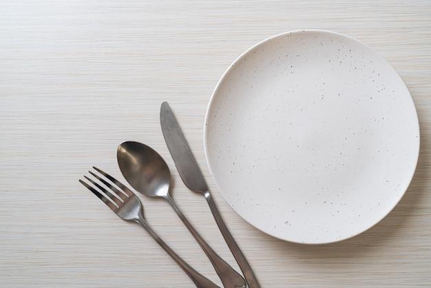 Lege plaat of schotel met mes, vork en lepel op houten tafel