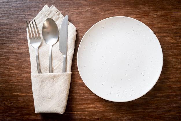 Lege plaat of schotel met mes, vork en lepel op houten tegelachtergrond