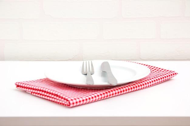 Lege plaat op rood tafelkleed over lijst met de achtergrond van het baksteenbehang