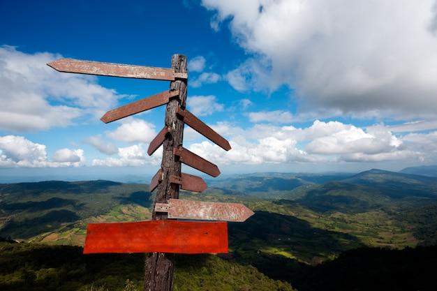 Lege plank en houten gidspost op de blauwe hemel met bergachtergrond.