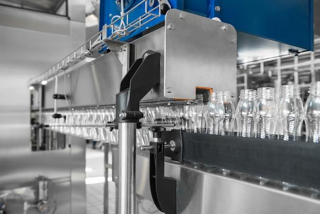 Lege plastic flessen op transportband. apparatuur in de zuivelfabriek