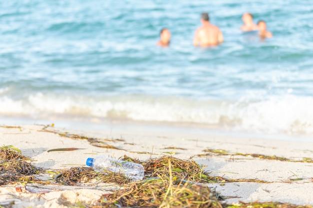 Lege plastic flessenwater strand gevuld met zeewier, afval en afval op vuile zandstrand met mensen in zee op