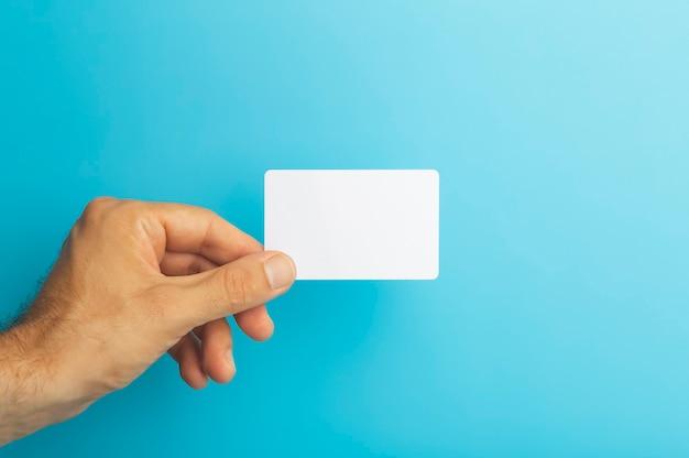 Lege plastic kaart in de hand op gekleurde achtergrond-id of creditcard isoleert foto van hoge kwaliteit