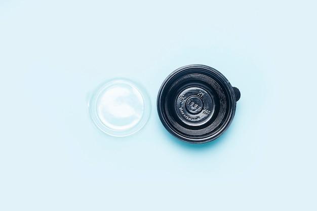 Lege plastic kom met open deksel op een lichtblauwe achtergrond