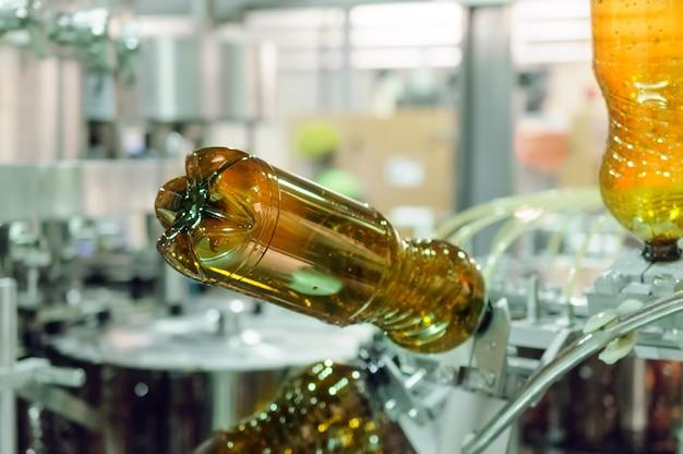 Lege plastic pet-flessen in een vulmachine. brouwproductie, abstracte industriële achtergrond.
