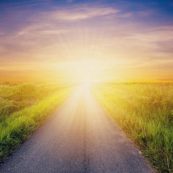 Lege plattelandsweg en zonsonderganghemelachtergrond.