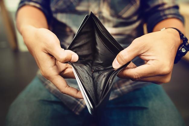 Lege portefeuille (geen geld) in de handen van een zakenman