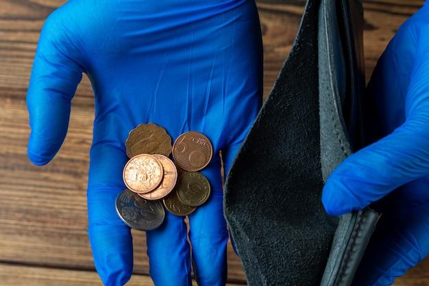 Lege portemonnee en hand met enkele munten