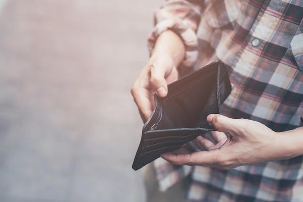 Lege portemonnee (geen geld) in de handen van een man. kostenbeheersing uitgaven armoede in concept