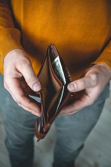 Lege portemonnee in de handen van een jonge man
