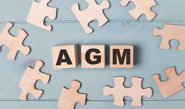 Lege puzzels en houten kubussen met de tekst agm annual general meeting liggen op een lichtblauwe achtergrond.