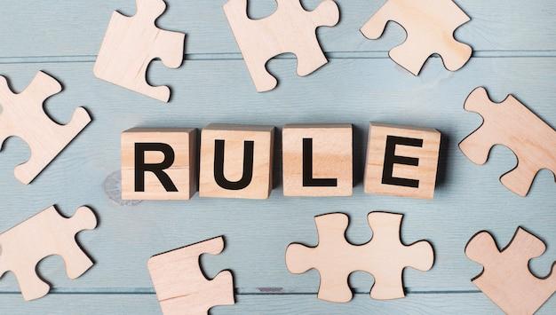 Lege puzzels en houten kubussen met de tekst rule liggen op een blauwe achtergrond.