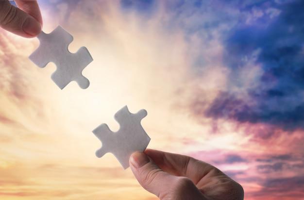 Lege puzzels in handen op hemelachtergrond